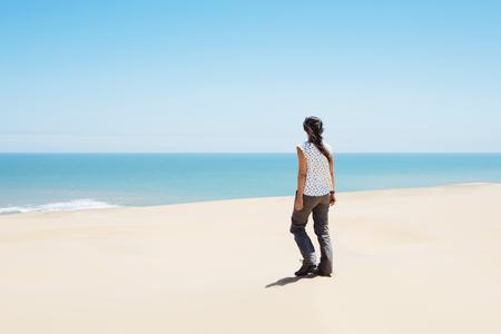 Namibia, Namib desert, Swakopmund, woman walking among the dunes of the desert to the sea LANG_EVOIMAGES