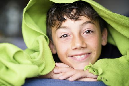 Portrait of smiling boy under a green blanket LANG_EVOIMAGES