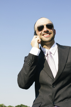 Smiling businessman with sunglasess talking on phone LANG_EVOIMAGES
