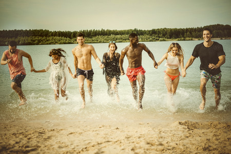 Germany, Haltern, seven friends running hand in hand out of Lake Silbersee having fun