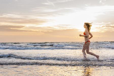 Woman wearing bikini jogging at the sea
