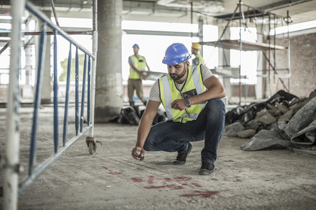spaying: Construction worker spaying marks on floor in construction site