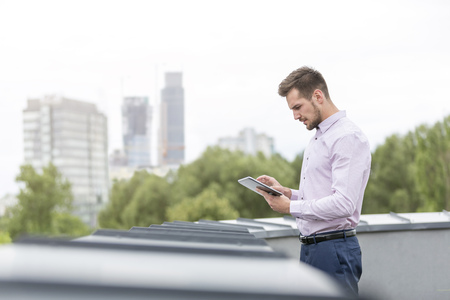 Young businessman on roof terrace using digital tablet LANG_EVOIMAGES