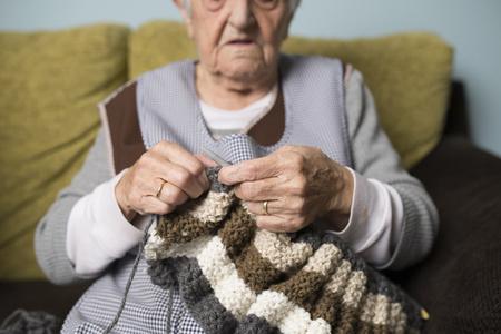 living room sofa: Senior woman knitting
