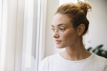 Young woman with eyeglasses looking out of her window LANG_EVOIMAGES