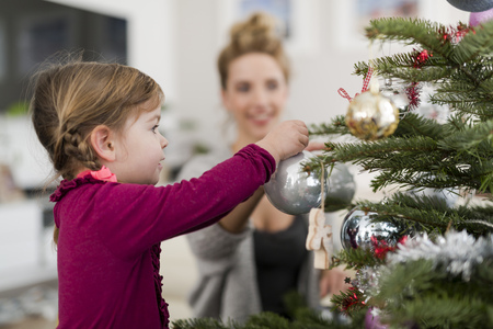 decorating: Little girl decorating Christmas tree with her mother in the living room