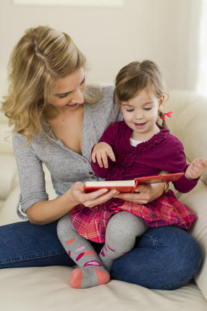 living room sofa: Little girl sitting on her mothers lap watching a book