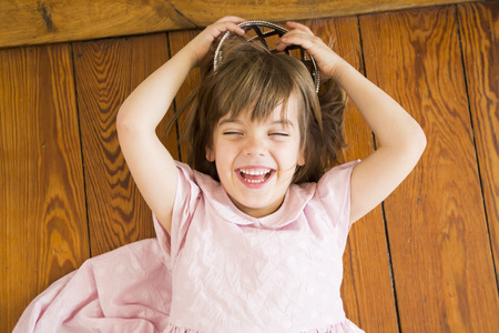 Portrait of laughing little girl dressed up as a princess