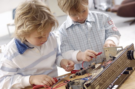 Two little boys disassembling an old radio LANG_EVOIMAGES
