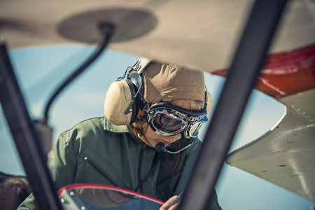 Germany, Dierdorf, Boy sitting in biplane wearing old pilot outfit LANG_EVOIMAGES