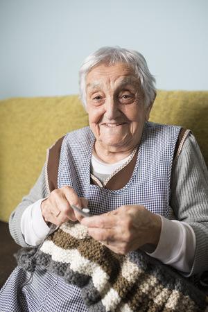living room sofa: Portrait of smiling senior woman knitting LANG_EVOIMAGES