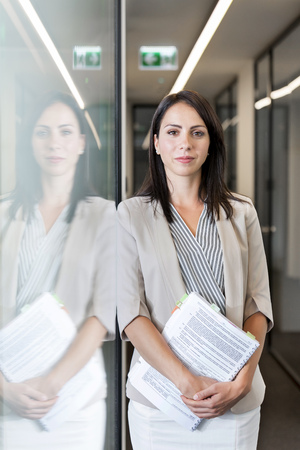 Young businesswoman standing in corridor, holding files LANG_EVOIMAGES