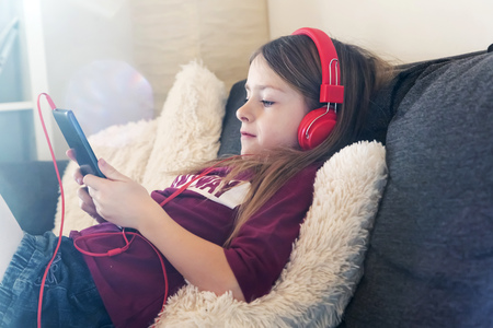 living room sofa: Girl sitting on the couch listening music with headphones and digital tablet LANG_EVOIMAGES