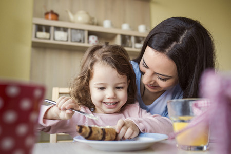 one parent: Portrait of little girl and her mother at breakfast table LANG_EVOIMAGES