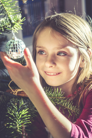 decorating: Portrait of smiling girl decorating Christmas tree