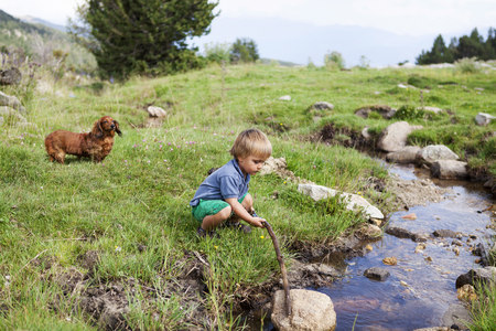 hounds: Spain, Cerdanya, little boy playing on a meadow at a brook