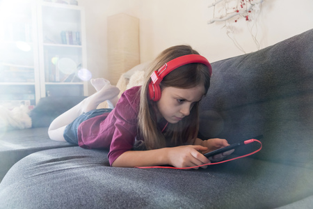 living room sofa: Girl lying on the couch listening music with headphones and digital tablet LANG_EVOIMAGES