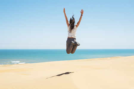 Namibia, Namib desert, Swakopmund, woman jumping in the desert with the sea in the background