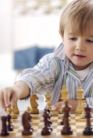 Portrait of little boy playing chess LANG_EVOIMAGES