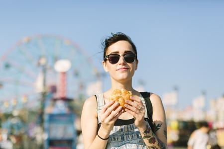 USA, New York, Coney Island, young woman eating a hamburger LANG_EVOIMAGES