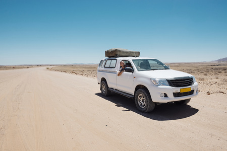 Namibia, Namib desert, Swakopmund, man on a 4x4 car with tent on the roof in a dusty road