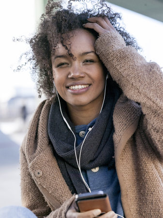 Portrait of smiling young woman  hearing music with earphones