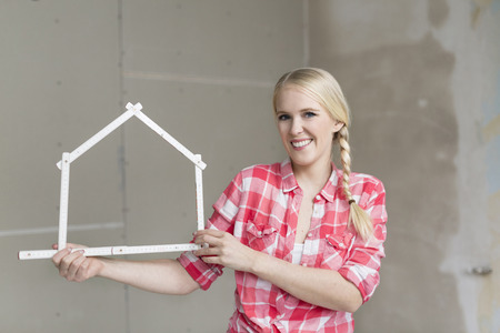 unfinished building: Smiling young woman holding pocket rule in shape of a house on construction site