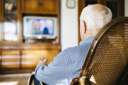 hairline: Back view of senior man sitting in his rocker watching television