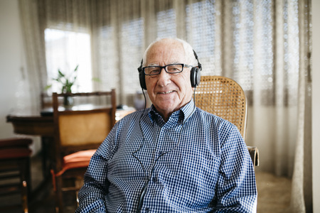 Portrait of smiling senior man hearing music with headphones at home LANG_EVOIMAGES
