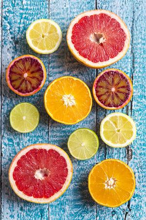 sorts: Sliced citrus fruits on light blue wood LANG_EVOIMAGES