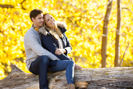 Happy couple enjoying autumn in a forest sitting on a trunk