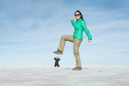 suppression: Bolivia, Salar de Uyuni, woman kicking small man, visual illusion