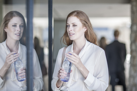 man drinking water: Young business woman drinking water