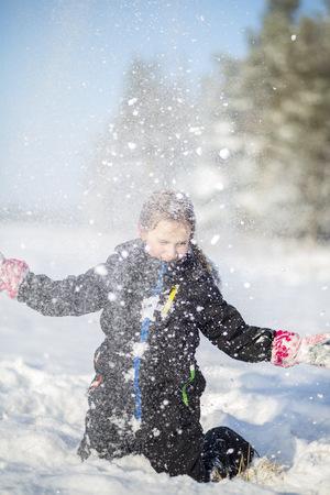 arrodillarse: Chica lanzando nieve en el aire LANG_EVOIMAGES