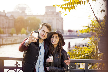 man drinking water: Germany, Berlin, young couple at River Spree with coffee to go LANG_EVOIMAGES