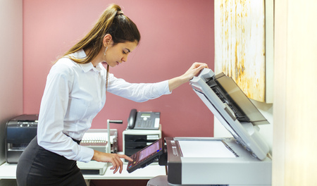Young businesswoman working at copying machine in the office