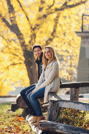 Happy couple sitting on wooden railing in autumnal park