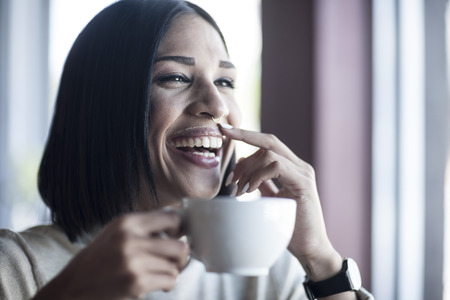 nose close up: Portrait of laughing woman with milk moustache holding cup of coffee LANG_EVOIMAGES