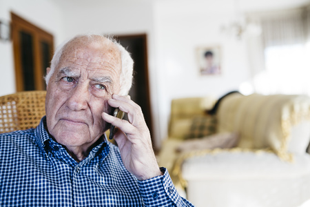 hairline: Portrait of senior man telephoning with smartphone at home