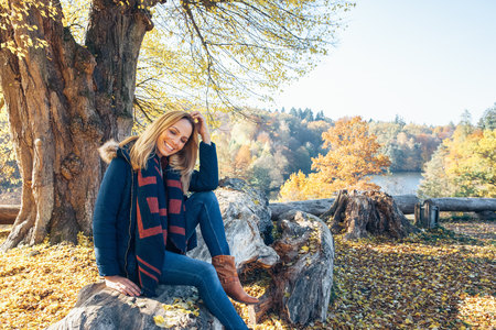 Smiling woman enjoying autumn in a forest sitting on a trunk