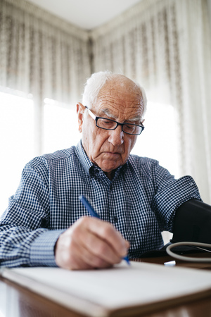 hairline: Senior man controlling his blood pressure and writing down the result LANG_EVOIMAGES