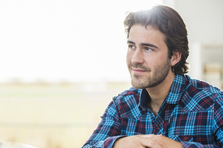 Portrait of relaxed man with brown hair wearing checked shirt LANG_EVOIMAGES