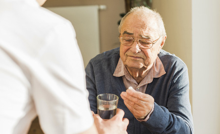man drinking water: Senior man getting tablet and glass of water