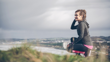 cowering: Sporty mid adult woman on cliff looking at sea