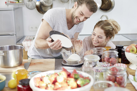 Couple in kitchen pouring sugar into bowl