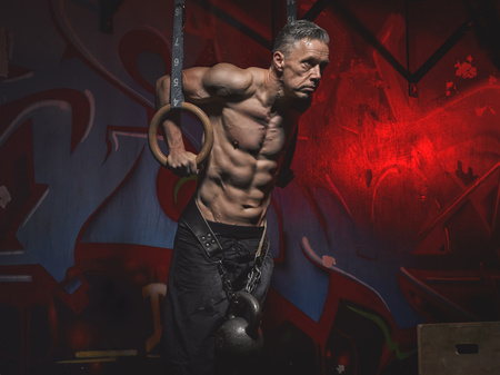 motivations: Mature crossfit athlete doing ring dips