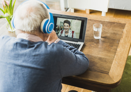man drinking water: Senior man using laptop and headphones for skyping with his grandson LANG_EVOIMAGES
