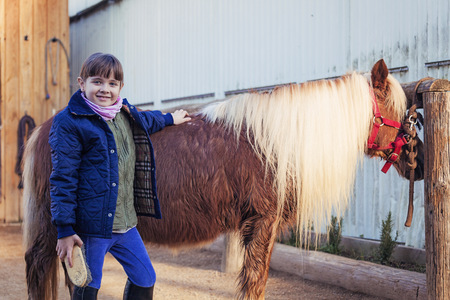 Portrait of smiling girl grooming pony