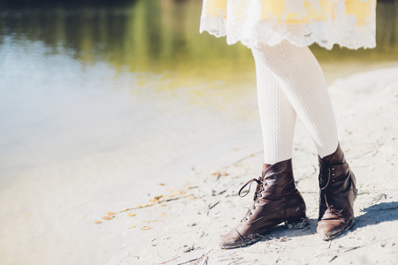 skirts: Legs of old-fashioned styled woman at waters edge LANG_EVOIMAGES