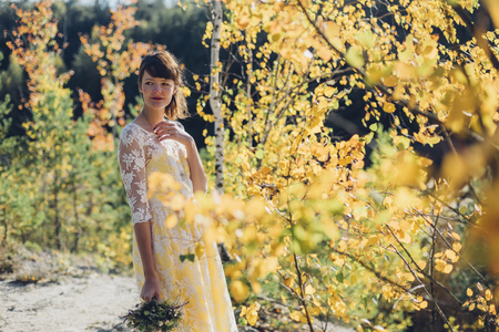 marrying: Portrait of young woman with bouquet in autumnal nature LANG_EVOIMAGES